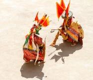 as monges executam uma batalha simbólica durante a dança mascarada e trajada religiosa do mistério do budismo tibetano durante a  fotografia de stock royalty free