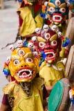 As monges não identificadas com cilindros executam uma dança mascarada e trajada religiosa do mistério do budismo tibetano imagem de stock