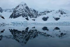 As montanhas e as geleiras da Antártica refletem na baía azul do espelho no dia nebuloso foto de stock