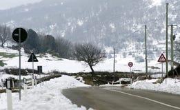 As montanhas nevado da paisagem, sinais de estrada, árvores, limparam a estrada Imagens de Stock