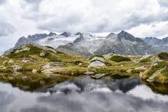 As montanhas refletiram em um lago rippled nos cumes suíços, com a Imagem de Stock