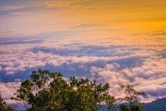 As montanhas são cobertas pela névoa e pelo nascer do sol da manhã Imagens de Stock