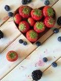 As morangos e os mirtilos frescos na lareira dão forma à cesta Fotografia de Stock