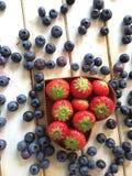 As morangos e os mirtilos frescos na lareira dão forma à cesta Imagens de Stock