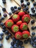 As morangos e os mirtilos frescos na lareira dão forma à cesta Imagem de Stock