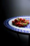 As morangos em uma tabela do mosaico na janela iluminam-se Imagens de Stock