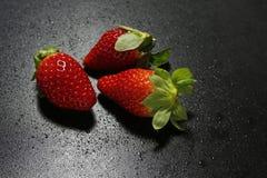As morangos frescas com água deixam cair no fundo preto Foto de Stock