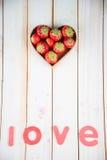 As morangos frescas na lareira dão forma à cesta na mesa de cozinha Fotos de Stock