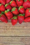 As morangos orgânicas maduras dispersaram do alimento saudável de madeira do fundo Weathered na colheita de limpeza do verão Imagens de Stock