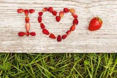 As morangos são apresentadas nas letras em um fundo da grama verde e da placa Foto de Stock Royalty Free
