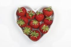 As morangos vermelhas em um coração do amor deram forma ao prato Fotos de Stock Royalty Free