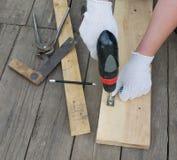 As mãos do carpinteiro usando a broca Fotos de Stock