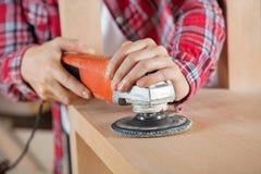 As mãos do carpinteiro usando Sander On Wooden Shelf Foto de Stock Royalty Free