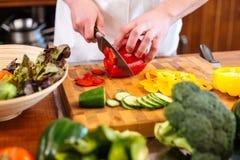 As mãos do cozinheiro chefe cozinham o corte da pimenta de sino vermelha na tabela Fotos de Stock Royalty Free