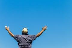 As mãos do homem aumentaram o azul Fotografia de Stock Royalty Free