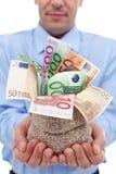 As mãos do homem de negócios com euro- cédulas em um dinheiro ensacam Foto de Stock Royalty Free