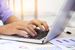 As mãos do homem de negócios que datilografam no teclado do portátil Imagens de Stock