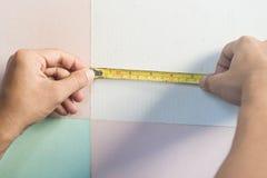 As mãos do homem que guardam a fita métrica Fotografia de Stock
