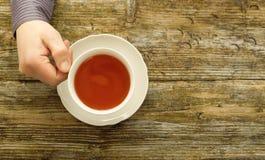 As mãos masculinas do copo de chá que guardam o café apresentam a vista superior de madeira Fotos de Stock Royalty Free