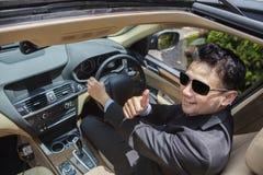 As mostras bem sucedidas do homem de negócios APROVAM assinam dentro o carro Foto de Stock Royalty Free