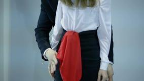 As mostras do mágico enganam com lenço e a mulher vermelhos no fundo escuro filme