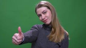 As mostras modelo louras alegres respeitam gesticular o sinal do polegar-acima isolado no fundo verde do chromakey video estoque
