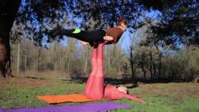 As mulheres acoplam o acroyoga praticando no parque no por do sol vídeos de arquivo