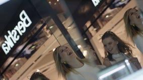 As mulheres alegres andam após o grande espelho na janela de loja da forma vídeos de arquivo