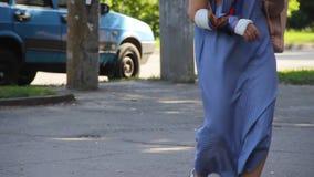 As mulheres andam abaixo da rua em um dia de verão Um tem uma cinta ou um emplastro no braço, uma fratura de osso A cara n?o ? vi filme