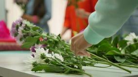 As mulheres aprendem fazer o design floral sob a orientação de um profissional Um grupo de jovens mulheres na classe de video estoque