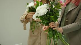 As mulheres aprendem fazer o design floral sob a orientação de um profissional Um grupo de jovens mulheres na classe de filme