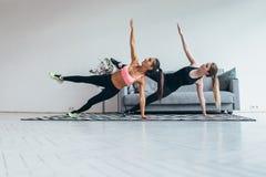 As mulheres aptas que fazem a prancha lateral exercitam pilates praticando em casa imagem de stock royalty free