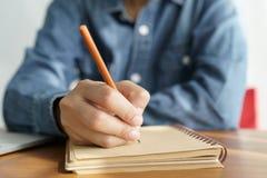 As mulheres asiáticas tomam notas com um lápis no escritório, funcionamento da mulher de negócio fotografia de stock