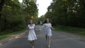 As mulheres atrativas novas vestiram-se no branco que corre o pé desencapado em uma estrada secundária da floresta que guarda as  vídeos de arquivo