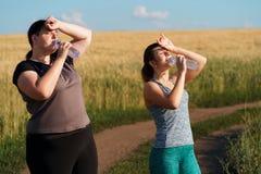 As mulheres bebem a água e o resto após movimentar-se exterior fotos de stock
