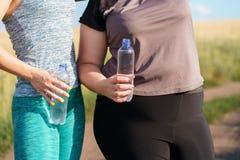 As mulheres bebem a água e o resto após movimentar-se exterior imagens de stock