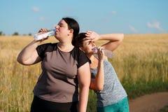 As mulheres bebem a água e o resto após movimentar-se exterior fotografia de stock royalty free
