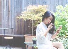 As mulheres bebem o café no jardim da manhã fotos de stock
