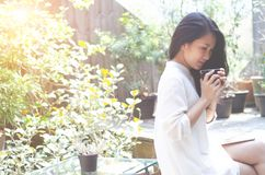 As mulheres bebem o café no jardim da manhã fotos de stock royalty free