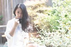 As mulheres bebem o caf? no jardim da manh? imagem de stock