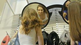 As mulheres bonitas da vista inferior gerenciem ao redor no espelho com os sacos video estoque