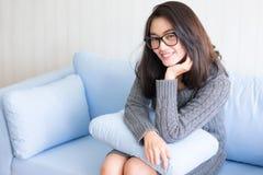 As mulheres bonitas que sentam-se para relaxam na sala de visitas em casa imagens de stock