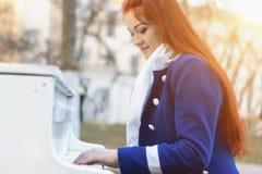 As mulheres caucasianos europeias com cabelo vermelho sorriem e jogam o piano no parque no por do sol A m?sica cl?ssica moderna e fotografia de stock