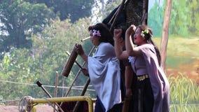 As mulheres Cheering na tradição tailandesa vestem-se ao lado do rio, alegremente e dançando ao conflito pelo barco no templo de  filme