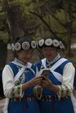 As mulheres chinesas que vestem uma minoria tradicional do Bai attire usando um smartphone em Lijiang, Yunnan imagens de stock royalty free