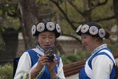 As mulheres chinesas que vestem uma minoria tradicional do Bai attire usando um smartphone em Lijiang, Yunnan imagem de stock royalty free