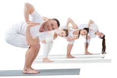 As mulheres com o instrutor que pratica a ioga revolvida da cadeira levantam em esteiras foto de stock