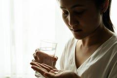 As mulheres comprimidas entregam a medicina da posse com um vidro do conceito da recuperação da água, dos cuidados médicos e da m fotos de stock