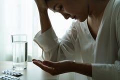 As mulheres da dor de cabeça entregam a medicina da posse com um vidro do conceito da recuperação da água, dos cuidados médicos e imagem de stock