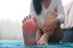 As mulheres da dor da lesão no calcanhar do pé tocam em seu pé conceito doloroso, dos cuidados médicos e da medicina fotos de stock